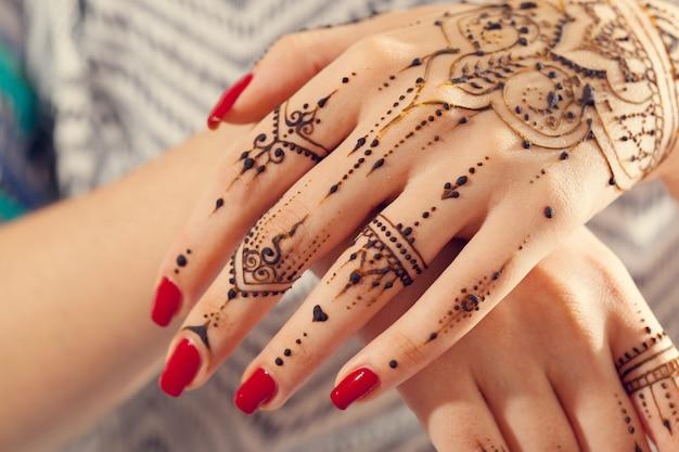Rode gemanicuurde handen met mehndi