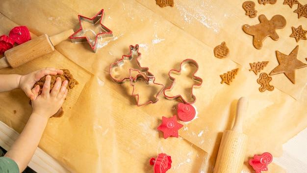 Rode gemberbroodvormen en deeg die op bruin bakpapier leggen. klaar maken voor kerstmis.