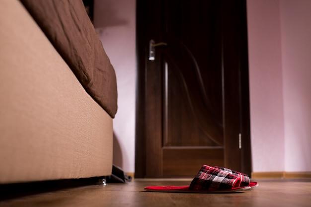 Rode geruite pantoffels naast bank. paar pantoffels dichtbij bed. ze begroeten je elke ochtend. warmte van thuis.