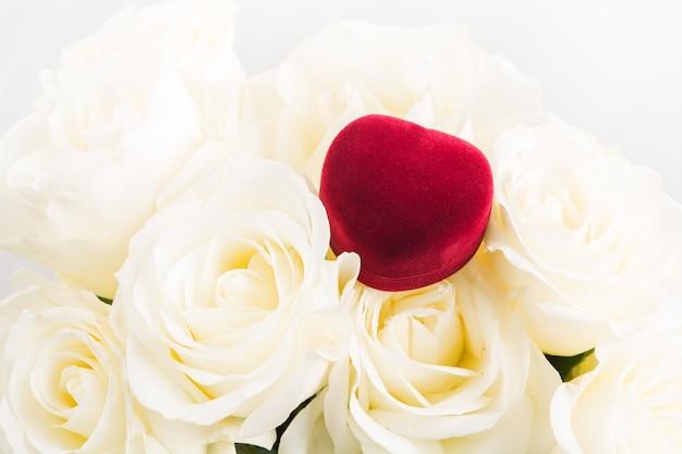 Rode geschenk juwelendoosje op boeket witte rozen