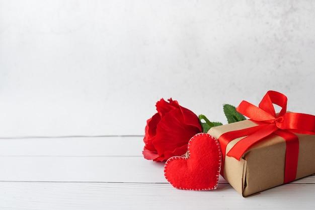 Rode geschenk of huidige doos met boog lint, bloem roos en hart op witte houten achtergrond, wenskaart voor valentijnsdag.