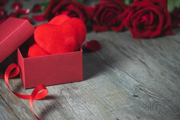 Rode geschenkdoos binnenin is er een rood hartkussen, geplaatst op een grijze houten vloer, het bovenaanzicht en kopieergebied, valentijnsdagthema