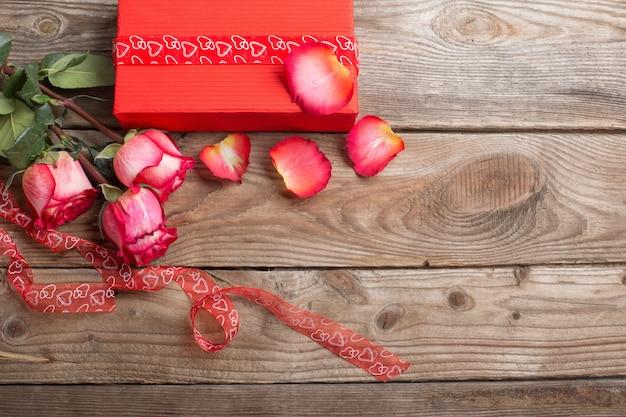 Rode geschenkdoos en boeket rozen op houten achtergrond