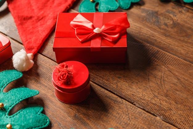 Rode geschenkdoos en kerstmuts op houten achtergrond