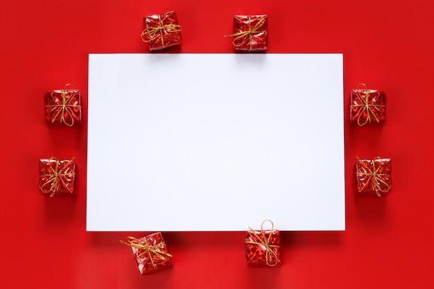 Rode geschenkdoos en lege papieren notitie op rode achtergrond.