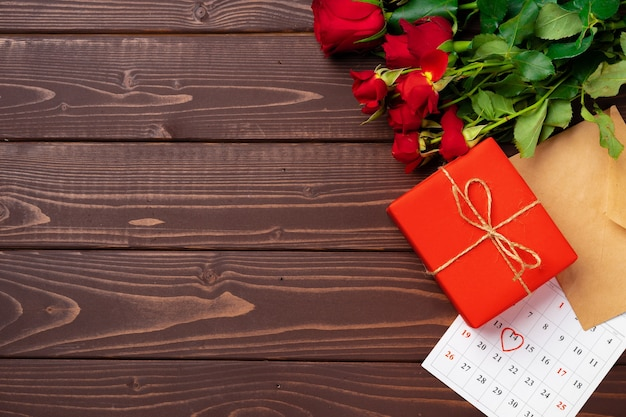 Rode geschenkdoos en rode rozen op houten bovenaanzicht