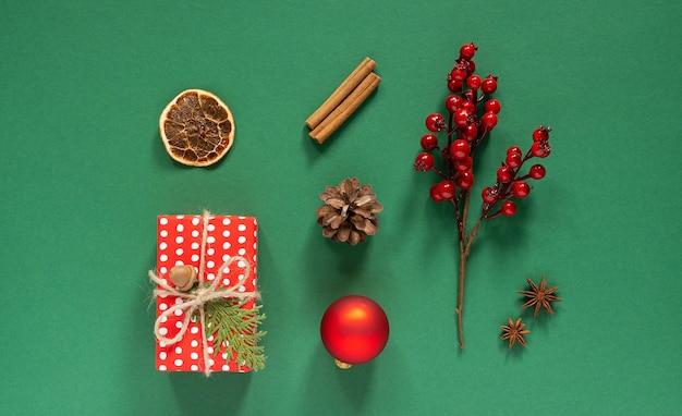 Rode geschenkdoos en thuja-twijgen met kerstboomkegel