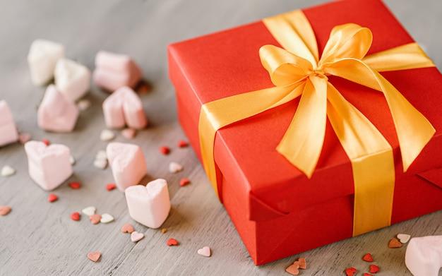 Rode geschenkdoos gebonden met een gouden lint. lint vastgebonden met een strik op een doos. g