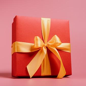Rode geschenkdoos gebonden met een gouden lint. lint vastgebonden met een strik op een doos.