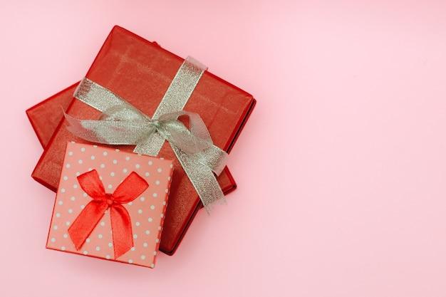 Rode geschenkdoos geïsoleerd op roze achtergrond met kopie ruimte