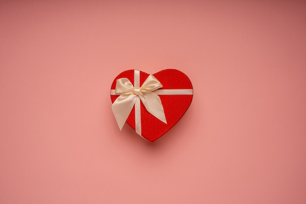Rode geschenkdoos, hartvorm, gebonden met een lint op de roze achtergrond, gefeliciteerd, cadeau, vakantie, verrassing