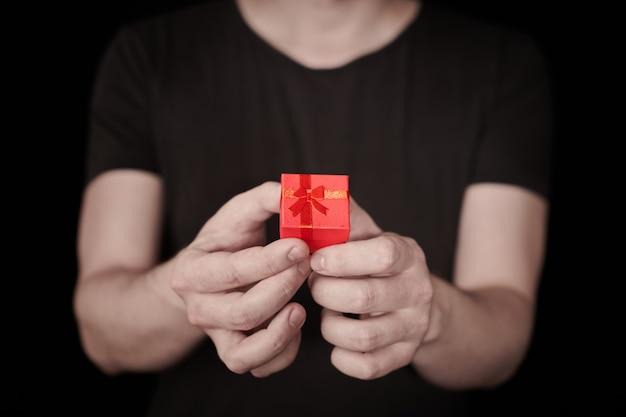 Rode geschenkdoos in de hand. valentijn cadeau. kleine jubileumgeschenkdoos van de mens. klein verrassingsconcept. zwarte achtergrond.