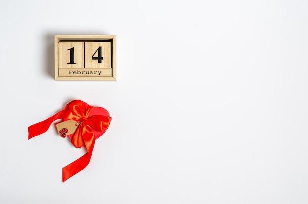 Rode geschenkdoos in de vorm van een hart en een label voor felicitaties en een houten kalender met de datum van 14 februari op wit