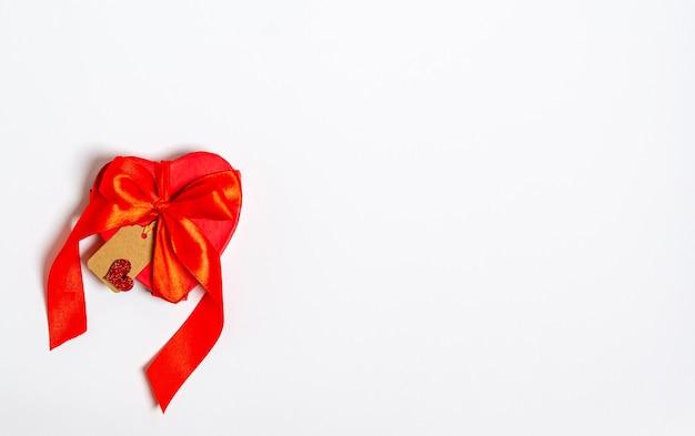 Rode geschenkdoos in de vorm van een hart met een label voor felicitaties op wit