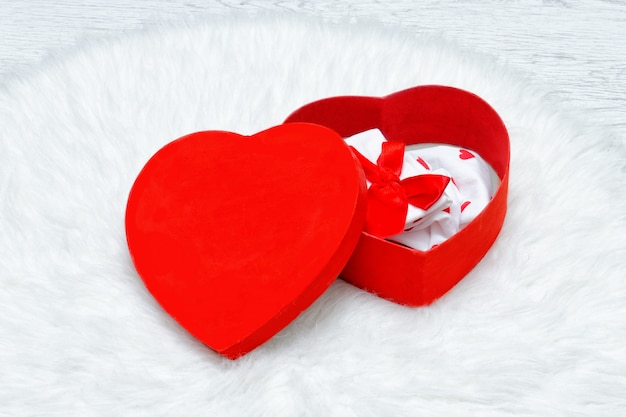 Rode geschenkdoos in de vorm van een hart. ondergoed en kaarsen