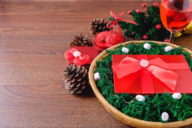 Rode geschenkdoos in een mand met kerstmis en een feest drankje