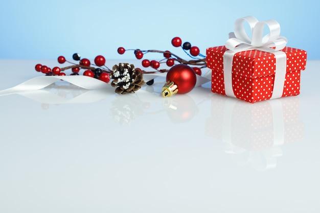 Rode geschenkdoos met kerstversiering op blauwe achtergrond
