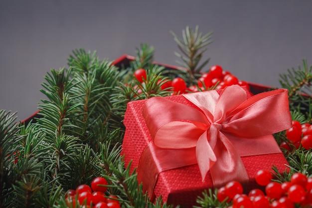 Rode geschenkdoos met satijnen roze strik, ondergedompeld in de naalden van een kerstboom versierd met rode bessen.