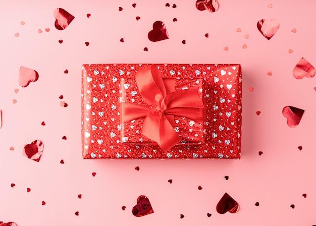 Rode geschenkdoos met touw strik op roze achtergrond met hartvormige confetti