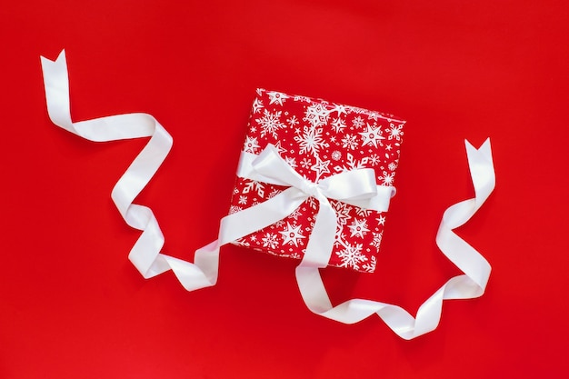 Rode geschenkdoos met wit satijnen lint geïsoleerd op rood