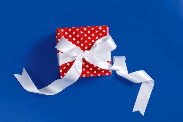 Rode geschenkdoos met witte satijnen lint boog geïsoleerd op blauw