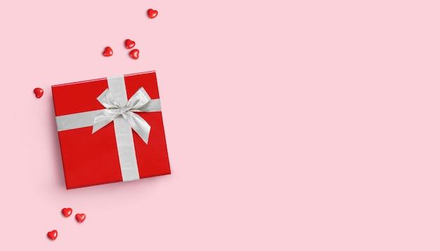 Rode geschenkdoos met zilveren lint op roze achtergrond. plat leggen. ruimte kopiëren