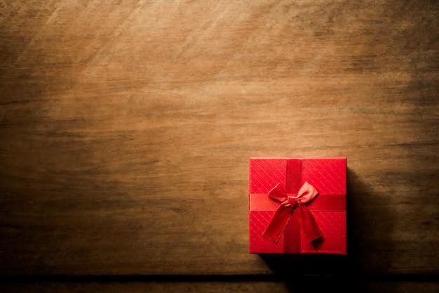 Rode geschenkdoos op houten plank. concept voor vakantie of valentijn dag.