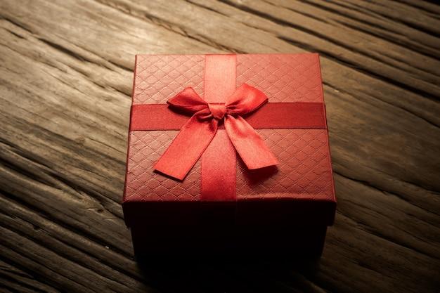 Rode geschenkdoos op houten plank. concept voor vakantie of valentijnskaartdag.