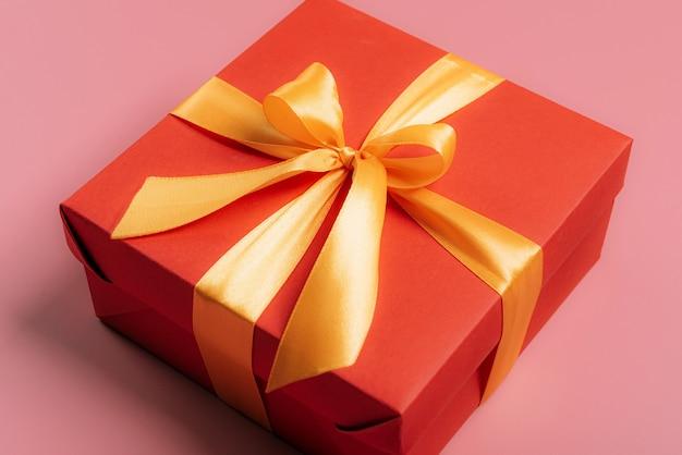 Rode geschenkdoos verbonden met een gouden lint