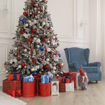 Rode geschenkdozen onder kerstboom en blauwe fauteuil achter