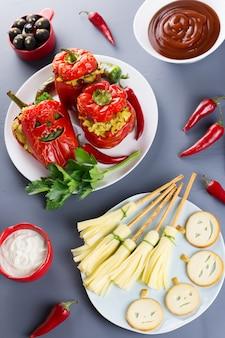 Rode gevulde paprika's met enge uitgesneden gezichten, heksenbezems van kaas en andere lekkernijen voor halloween