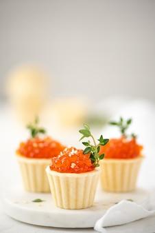 Rode gezouten zalmkaviaar in taartjes versierd met takjes tijm, close-up