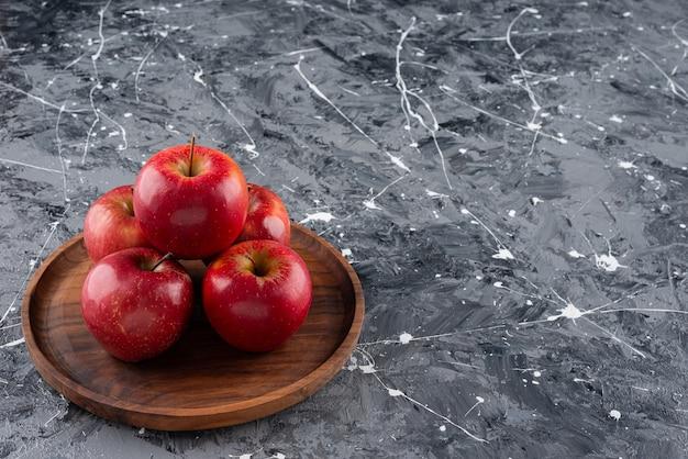 Rode glanzende hele appels die op houten plaat worden geplaatst.