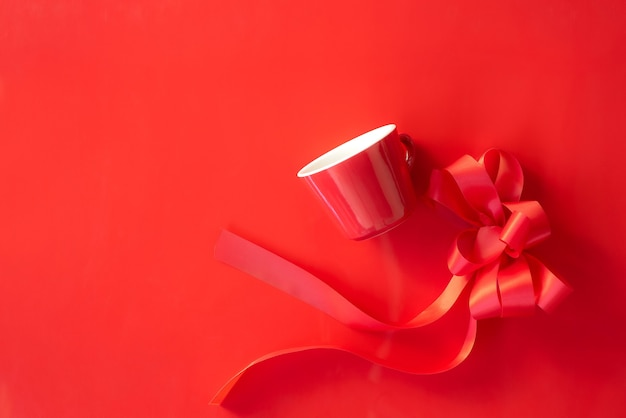 Rode glazen rode strik en geschenken op rode achtergrond bovenaanzicht