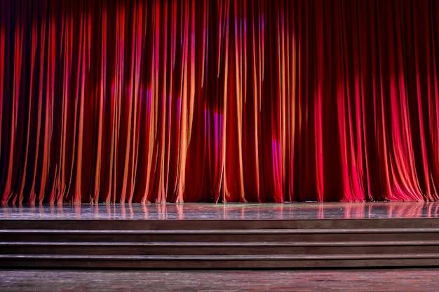 Rode gordijnen en houten podium.