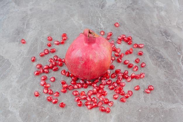 Rode granaatappel en zaden op stenen achtergrond.