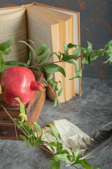 Rode granaatappel in houten kist met boek en bladeren