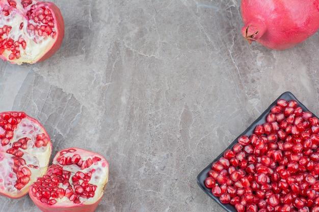 Rode granaatappels en plaat van zaden op stenen achtergrond.
