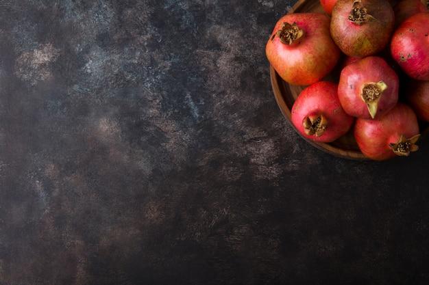 Rode granaatappels in een houten schotel op marmer