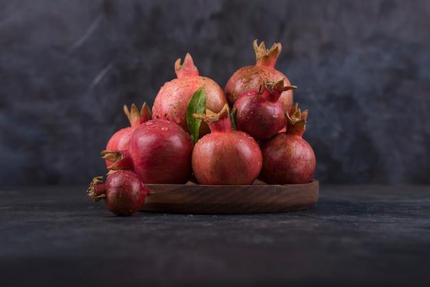 Rode granaatappels in een houten schotel