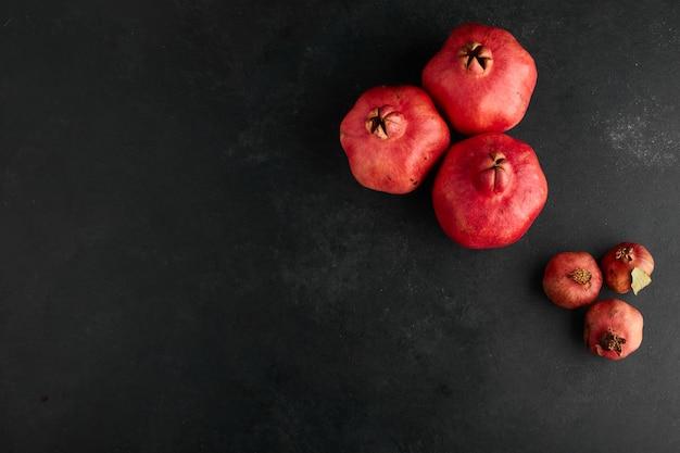 Rode granaatappels in kleine en grote vormen op de bovenhoek.