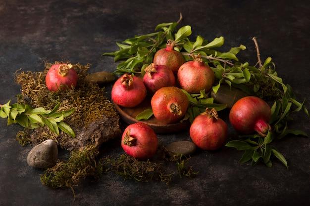 Rode granaatappels met groene bladeren op marmer