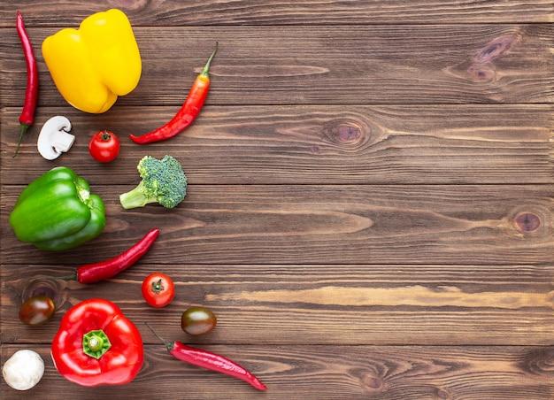 Rode, groene en gele paprika chili champignons en cherry tomaten op houten achtergrond