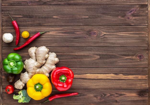 Rode, groene en gele pepers chili gember en cherrytomaatjes op houten achtergrond
