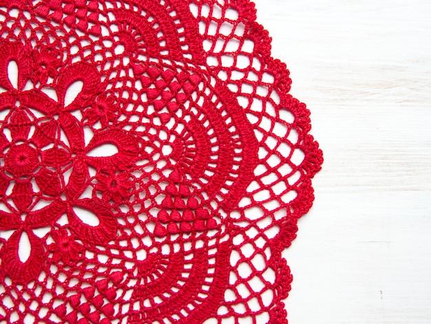 Rode haak kleedje over witte houten tafelblad bekijken