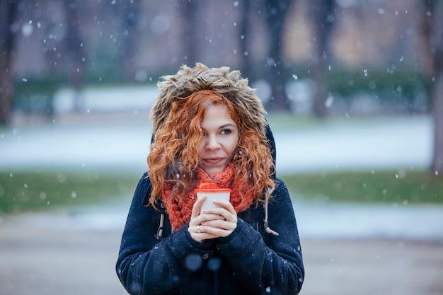 Rode haarvrouw die een kop van hete koffie houdt