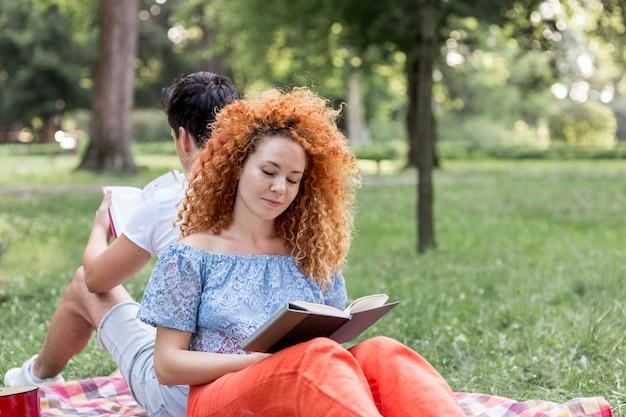 Rode haarvrouw die op een een picknickdeken ligt en een boek leest