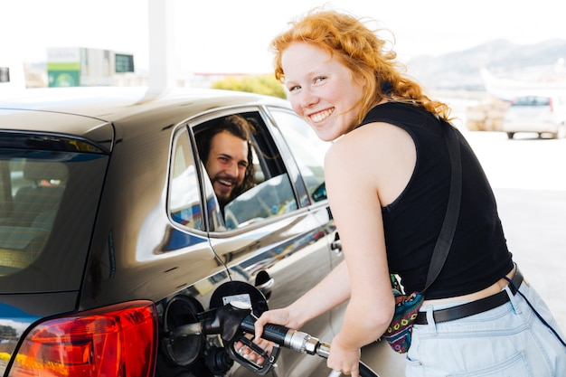 Rode haired jonge vrouwen vullende tank bij benzinepost