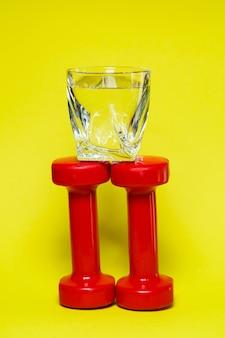 Rode halters, een glas water, gekleurde achtergrond, sport, energiedrank, apparatuur voor de sportschool