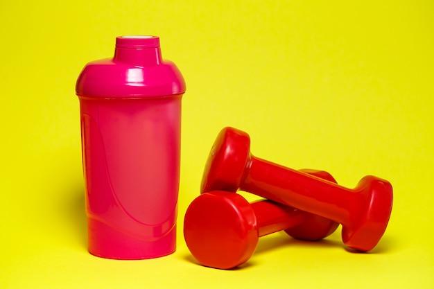 Rode halters, roze shaker, gekleurde achtergrond, sport, energiedrank, fitnessapparatuur